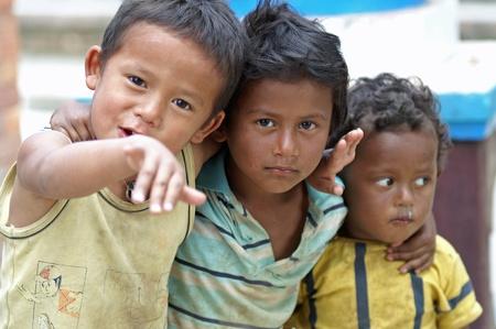 bambini poveri: Kathmandu, Nepal, 11 ottobre 2010: tre bambini che giocano per strada Editoriali