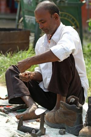 Kathmandu, Nepal, october 11, 2010: shoemaker works on the street