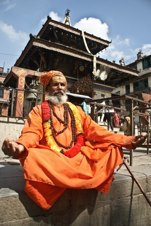 sadhu: Kathmandu, Nepal - October 10, 2010: Shaiva sadhu (holy man) seeking alms in front of a temple in Pashupatinath Editorial