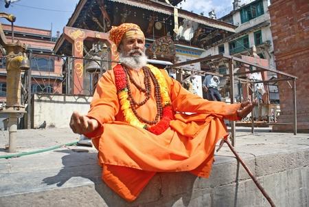 limosna: Katmand�, Nepal - 10 de octubre de 2010: Shaiva sadhu (hombre santo) pidiendo limosna en frente de un templo Editorial
