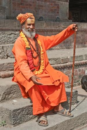 guru: Kathmandu, Nepal - October 10, 2010: Shaiva sadhu seeking alms in front of a temple
