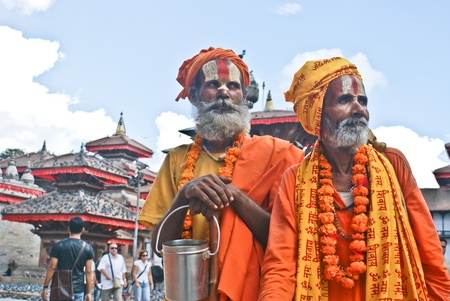 hindu temple: Kathmandu, Nepal - October 10, 2010: Two Shaiva sadhu seeking alms in front of a temple Editorial