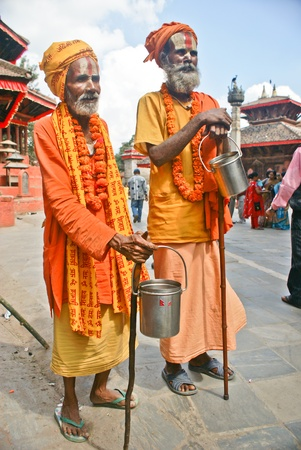 Kathmandu, Nepal - October 10, 2010: Two Shaiva sadhu walking alms in front of a temple