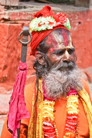 Kathmandu, Nepal - October 10, 2010: sadhu seeking alms in front of a temple