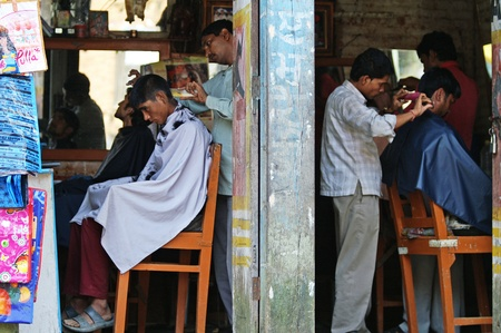 Kathmandu, Nepal - October 4, 2010: Two hairdresser cut the hair on the street Stock Photo - 10911673