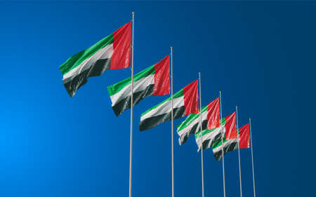 Several beautiful flags of United Arab Emirates waving in the blue sky. Symbol of UAE
