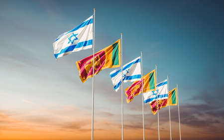 Israel and Sri Lanka flags waving in the wind against a sunset sky background. Relations between two countries in economic and diplomatic ways.