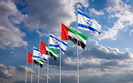 The UAE and Israeli flags fly together in the wind against the cloudy blue sky background. The concept of cooperation and competition in economics and politics. Flag of the Arab Emirates to the left of Israel.