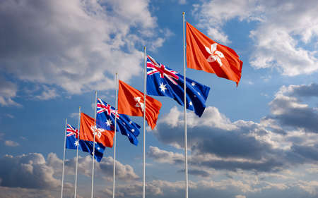The Aussie and Hong Kong flags fly together in the wind against the cloudy blue sky background. The concept of cooperation and competition in economics and politics. Flag of the Australia to the left of Hong Kong.
