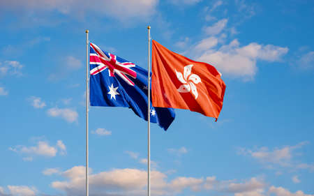 The Aussie and Hong Kong flags fly together in the wind against the blue sky. The concept of cooperation and competition in economics and politics. Flag of the Australia to the left of Hong Kong.