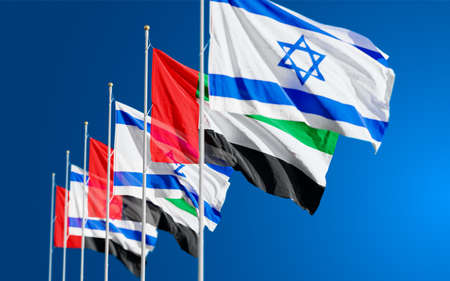 The UAE and Israeli flags fly together in the wind against the cloudy sky background. The concept of cooperation and competition in economics and politics. Flag of the Arab Emirates to the left of Israel. Banco de Imagens