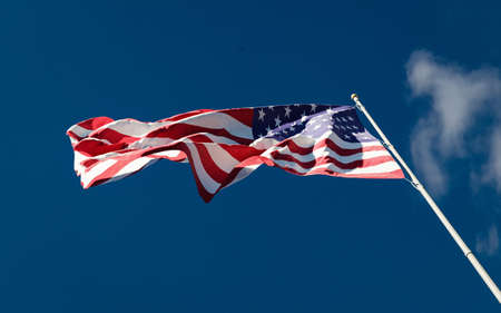US national flag waving in the wind against a blue sky background low angle close up. Stars and Stripes American Old Glory.