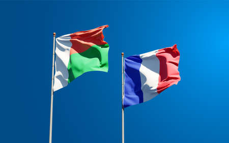 Beautiful national state flags of Madagascar and France together at the sky background. 3D artwork concept. Фото со стока