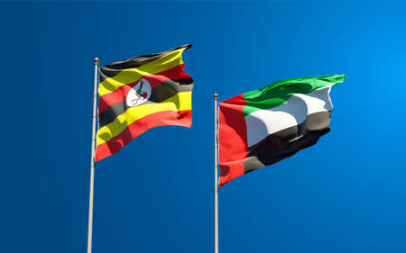 Beautiful national state flags of Uganda and UAE United Arab Emirates together at the sky background. 3D artwork concept.
