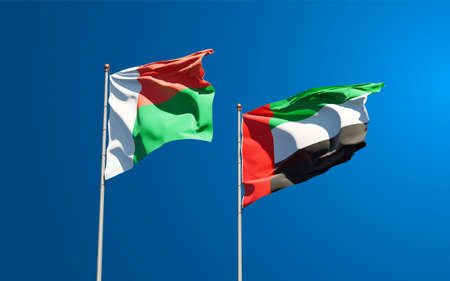 Beautiful national state flags of Madagascar and UAE United Arab Emirates together at the sky background. 3D artwork concept. Фото со стока