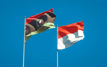 Beautiful national state flags of Libya and Indonesia together at the sky background. 3D artwork concept.