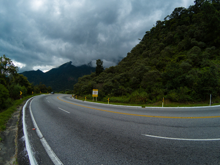 Road, mountains and cloudy sky
