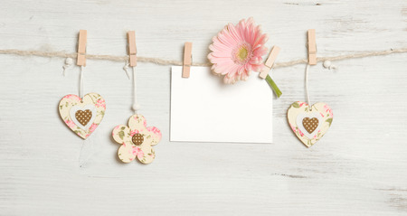 Heart, flowers and sign on clothesline on white wooden background Zdjęcie Seryjne
