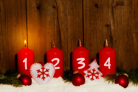 advent advent: Advent candles with snow in front of wood background