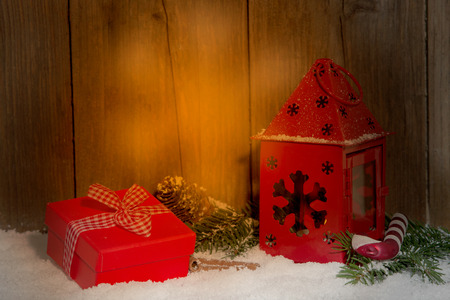 christmas present by candlelight in front of wooden background