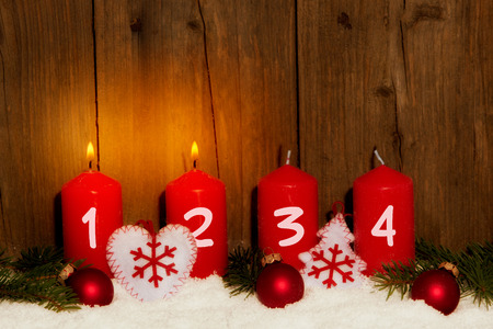 Advent candles with snow in front of wood background