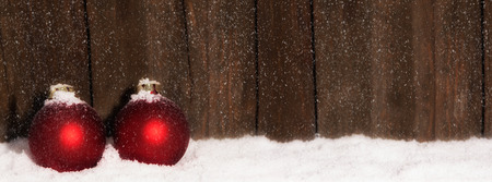 Christmas Balls in the snow in front of wooden background with copy space Zdjęcie Seryjne