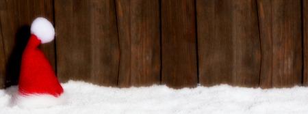 Weihnachtsmütze vor Holzhintergrund mit Textfreiraum Zdjęcie Seryjne - 46783097
