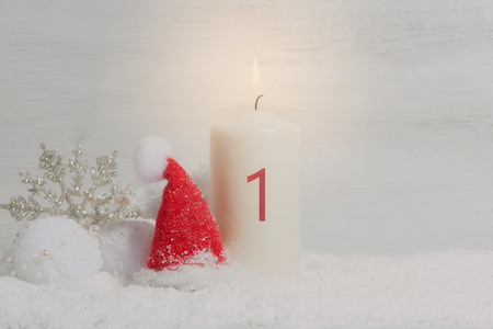 1. Advent, candle with number 1 and Santa hat in the snow