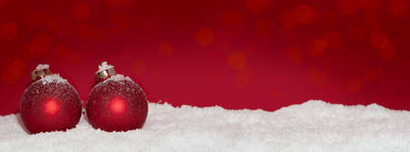 christmas decorations: red Christmas baubles in the snow with a red background