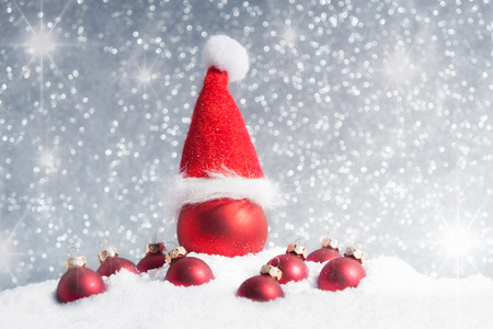 Christmas tree ball with santa hat in the snow with lots of little Christmas baubles Stock Photo - 47556578