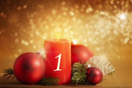 1. Advent, red candle with decoration, before bokeh background Archivio Fotografico