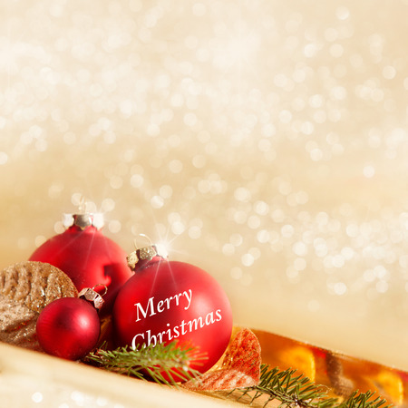 red Christmas baubles with Christmas decoration in front of golden bokeh background,