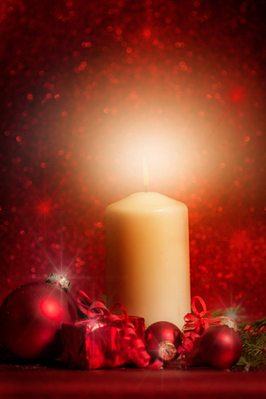 christmas candles: white candle  candle with Christmas decoration against red background with bokeh