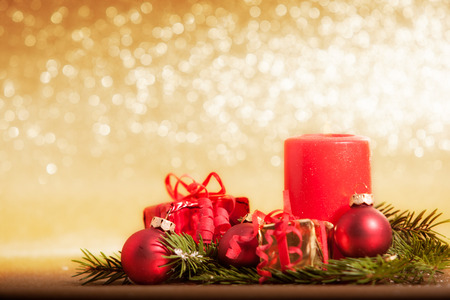 red candle decorated for Christmas with baubles and gifts in front of golden glittering background