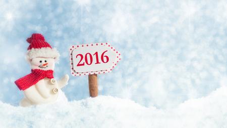 nouvel an: Bonhomme de neige avec panneau contre un ciel bleu avec des flocons de neige