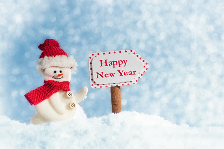 time of the year: Snowman with Signpost, Happy New Year, against a blue sky with snowflakes Stock Photo