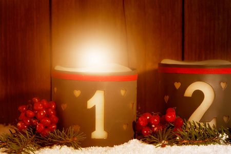 1. Advent, glowing candle with number 1 in front of wooden background Zdjęcie Seryjne