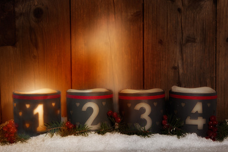 1. Advent, glowing candle with number 1 on wood background