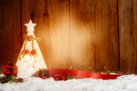 christmas time: Candle with light beam in a star shape in front of wooden background