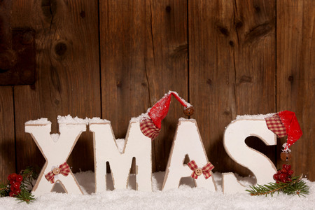Xmas, Wooden letters with Christmas hats in front of wooden background