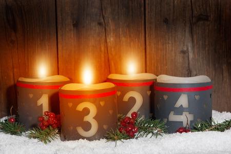 corona de adviento: 3. Adviento, las velas que brillan intensamente con números en frente de fondo de madera