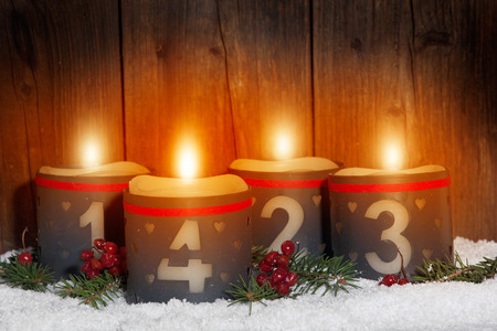 corona de adviento: 4. Adviento, las velas que brillan intensamente con números en frente de fondo de madera