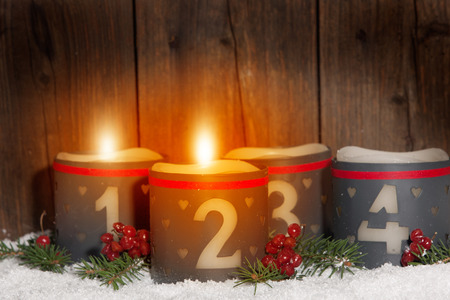 2. Advent, glowing candles with numbers in front of Wood background Imagens