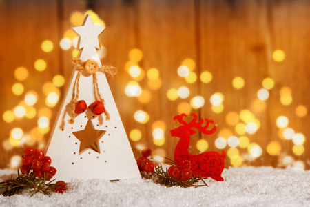 small wooden Christmas tree with star in the snow in front of wooden background with candlelight Stock Photo - 50055090