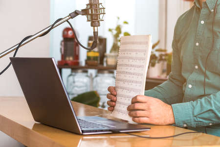 Close up of a young man sitting at the table with laptop. He has a microphone, he's teaching live music