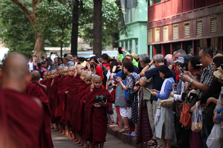 alms: Traditional Alms giving ceremony of distributing food to buddhist monks on the streets of Mahar Gandar Yone Monastery , Myanmar