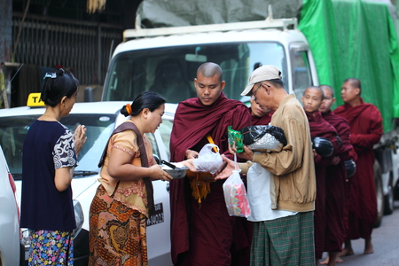 distributing: Traditional Alms giving ceremony of distributing food to buddhist monks on the streets of Yangon , Myanmar Editorial