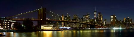 Panorama New York City downtown skyline and Brooklyn bridge at night. Banco de Imagens