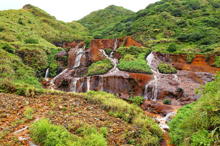Golden Waterfall flowing over rust-colored rocks & soil due to minerals from a former mining area in Taipei, Taiwan