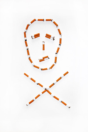 injurious: Symbol of the skull and bones of the cigarette butts Foto de archivo